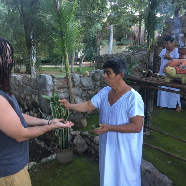 Jmen (Maya Shaman) blesses miniature Olmec head during ceremony